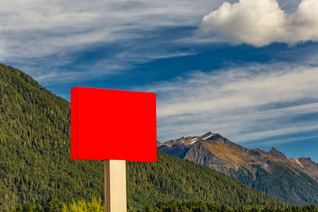 Blank red sign in the foreground and forest, mountains, blue sky with clouds in the background Stockfoto - 150297671