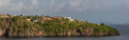 Beautiful panoramic aerial view of a cliff with some buildings and houses on it on St. Vincent island