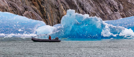 Single tourist sailing in a speed boat by a huge iceberg floating in a fjord. Alaska, USA