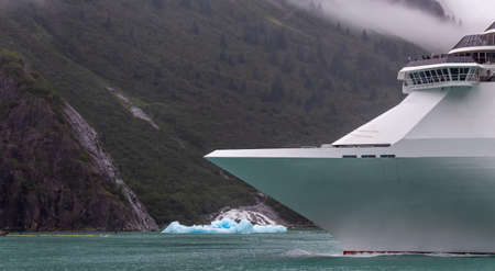 Cruise ship sailing in Alaska among icebergs. Ship's bow with mountains and cloud in the background. Stok Fotoğraf