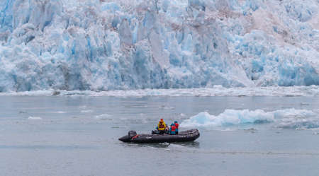 Tourists and a guide in a speedboat drifting among icebergs and a glacier behind it Stok Fotoğraf