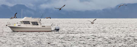 Fishing boat drifting in a bay with birds flying above it. Soft focus background. Alaska, USA Stok Fotoğraf