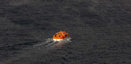View of a single orange life boat with some seamen inside sailing at sea. Caribbean sea.