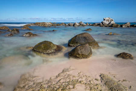 Beautiful rocky beach in Aruba. Three big stones in the foreground. Waves, sky and clouds in the background. Long exposure. Stok Fotoğraf