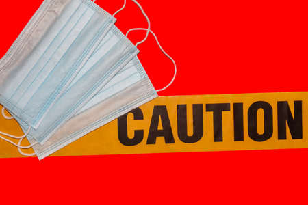 Facial protective masks on top of yellow caution tape. Isolated. Red background. Protection against viruses and bacteria. PPE. Quarantine area.