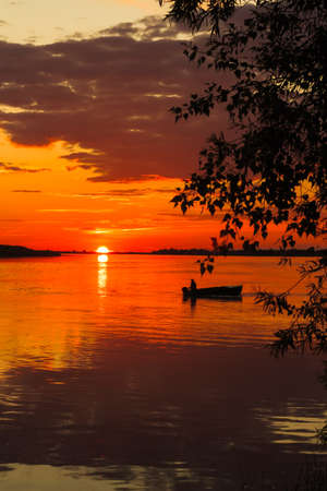 Beautiful sunset at a river with a boat sailing on it. Orange colors reflecting in the water.