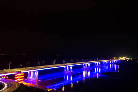 Perspective view of a bridge lit up at night. Barnaul City, Russia