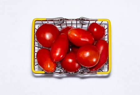Shot of tomatoes in shopping basket isolated on white background. Ripe tasty red tomatos in shopping basket. Top view. Tomato trading concept. Online shopping concept.