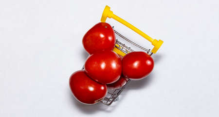 Shot of tomatoes in shopping cart isolated on white background. Top view. Ripe tasty red tomatos in shopping cart. Tomato trading concept. Online shopping concept. Copy space.