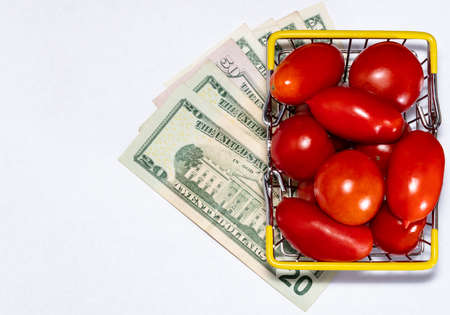 Shot of tomatoes in shopping basket isolated on white background with with various US dollar bills underneath it. Ripe tasty red tomatos in shopping basket. Top view. Tomato trading concept. Online shopping concept. Copy space. Stock fotó