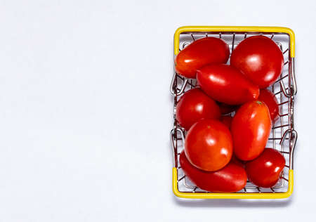 Shot of tomatoes in shopping basket isolated on white background with copy space. Ripe tasty red tomatos in shopping basket. Top view. Tomato trading concept. Online shopping concept. Copy space. Stock fotó