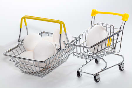 Fresh eggs in a shopping cart and a basket next to it. Eggs in a basked slightly out of focus. High angle view. Shopping, purchasing, and food delivery concept. White background. Close up shot. Isolated.
