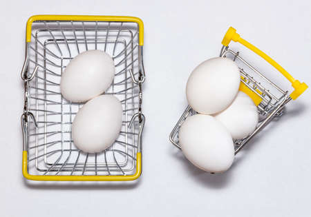 Fresh eggs in a shopping cart and a basket next to it. Top view. Shopping, purchasing, and food delivery concept. White background. Close up shot. Isolated.