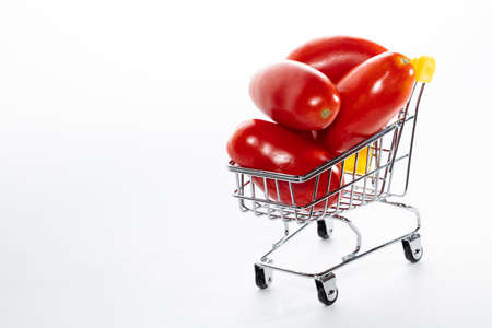 High angle shot of tomatoes in shopping cart isolated on white background. Ripe tasty red tomatos in shopping cart. Tomato trading concept. Online shopping concept. Copy space. Stock fotó