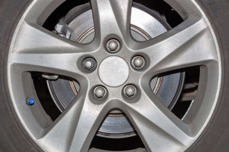 Car wheel on a car close-up, wheel tuning disk and tire in repair workshop