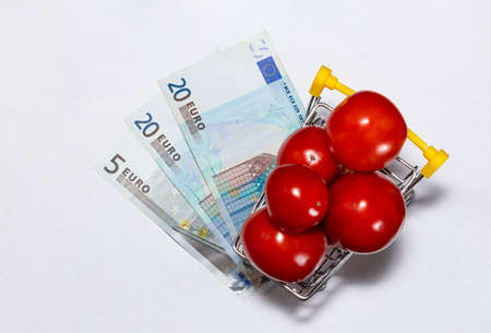 Shot of tomatoes in shopping cart isolated on white background with euro bills under it. Top view. Ripe tasty red tomatos in shopping cart. Tomato trading concept. Online shopping concept. Stockfoto