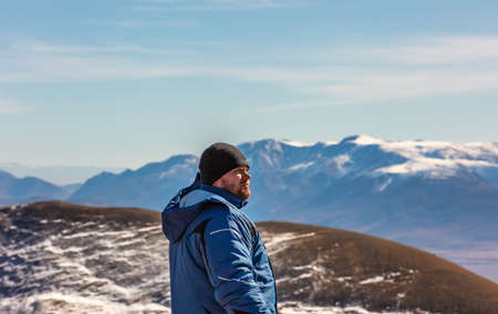 View of a tourist looking in the distance in the mountains. White snowy mountain ridge and beautiful blue cloudy sky as a background and slightly out of focus. Altai mountains, Siberia, Russia.