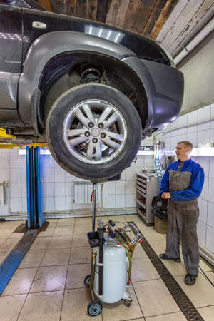 Car mechanic changes oil in a workshop. Mechanic standing next to the car and draining oil into a special cannister. Car is on the hydraulic lift.