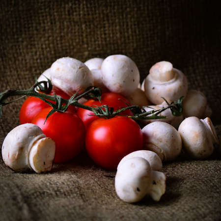 earthy: Earthy tomatoes and mushrooms on a rustic background Stock Photo