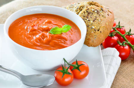 Tomato soup and crusty bread rolls Stock Photo