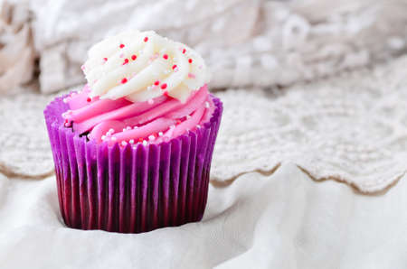 Pink cupcake with sprinkles on a fabric background. Stock Photo