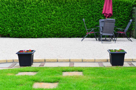 Gravel patio area in the garden with garden furniture