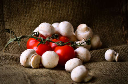 Rustic tomatoes and mushrooms on a hessian background Stock Photo