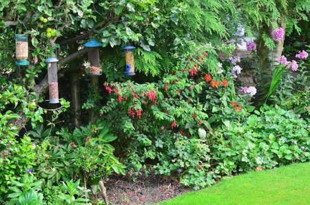 feeders: English country garden with bird feeders Stock Photo