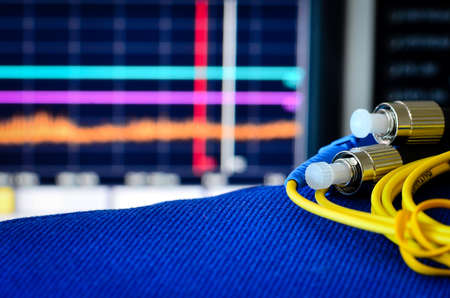 Fibre optic cable with spectrum analyser in the background Stock Photo