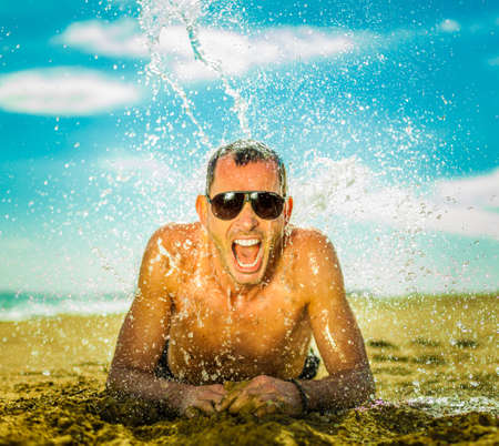 sunburn: sexy young man at a beach with a big splash of cool water