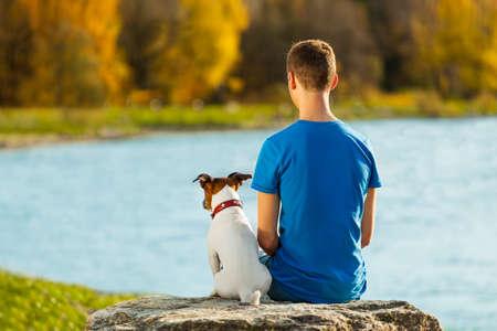 jongen en zijn hond zitten samen genieten van het uitzicht