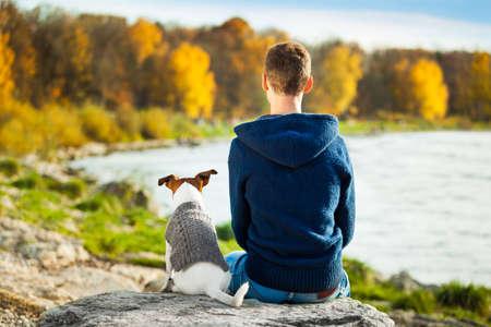 přátelé: Chlapec a jeho pes sedí společně se těší pohled na podzim