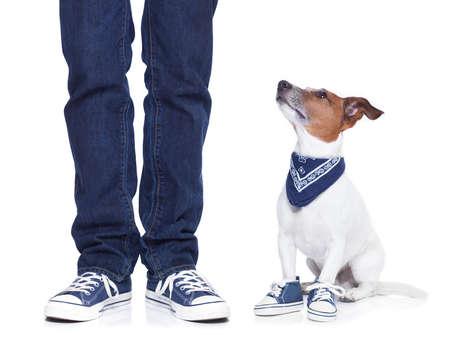 escarpines: dueño del perro con su perro ambos llevando zapatillas de deporte y una tabla de skate Foto de archivo