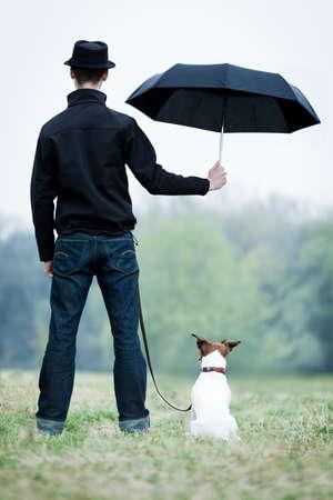 lluvia paraguas: la amistad entre el perro y el dueño de pie bajo la lluvia con paraguas