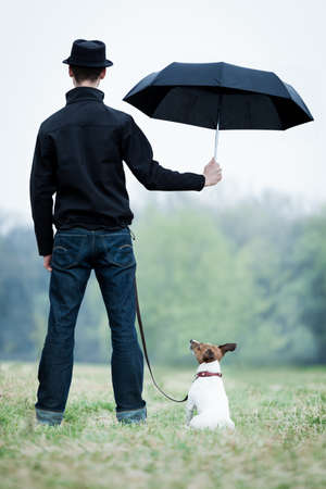 friendship between dog and owner standing in the rain with umbrella, dog looking up photo
