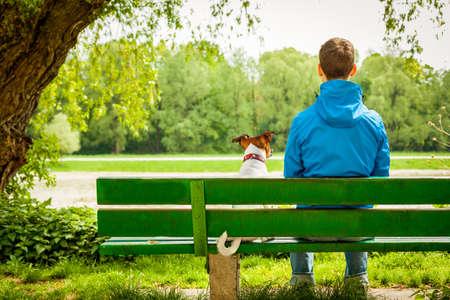 dog: 개는 주인과 은행에 앉아서 경치를 즐기고 스톡 사진