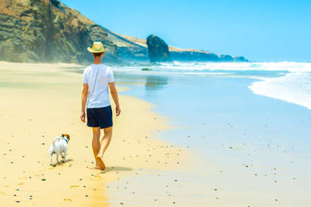 seaside: dog and owner walking at the beach on a paradise beach Stock Photo