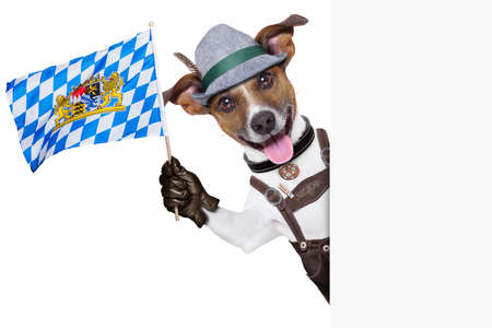 bavarian oktoberfest dog  smiling happy  and waving with bavarian flag besides a white blank banner or placard photo