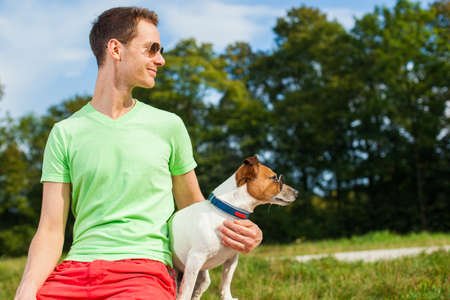 dog and owner observing together , sitting very close together having a good time outdoors photo