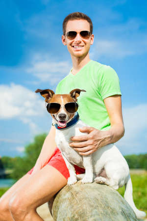man dog: dog and owner observing together , sitting very close together having a good time outdoors in the park Stock Photo