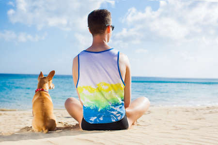 close together: dog and owner sitting close together at the beach on summer vacation holidays, watching sunset or sunrise Stock Photo