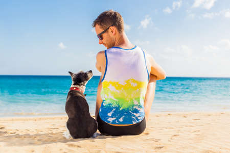 dog and owner sitting close together at the beach on summer vacation holidays Stock Photo