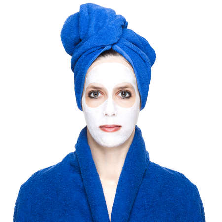 beauty woman face: young woman or girl  with beauty facial cream mask on face , towel and bathrobe as wellness treatment ,  isolated on white background