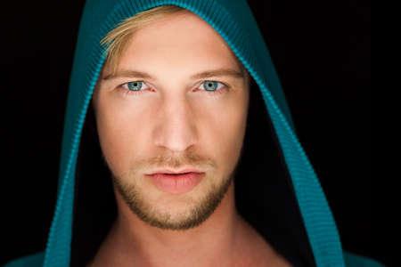 blonde yeux bleus: sexy jeune homme avec un sweat � capuche, close up yeux bleus portrait et cheveux blonds