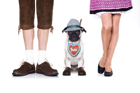 gingerbread heart: pug  dog with  gingerbread heart and bavarian couple of family owners , isolated on white background Stock Photo