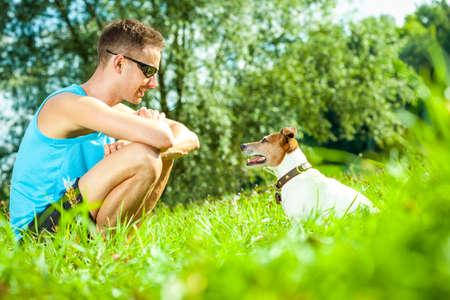 perro Jack Russell con el propietario, el entrenamiento exterior y al aire libre en el parque o en el prado, mirando a los ojos