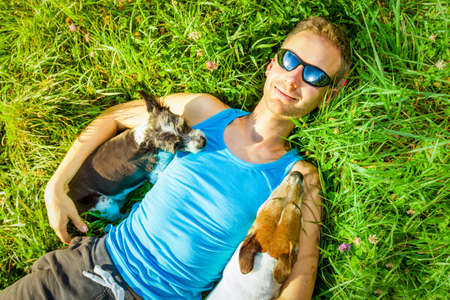 sunbath: jack russell dogs with owner relaxing at the park on the meadow grass, together embracing and hugging Stock Photo