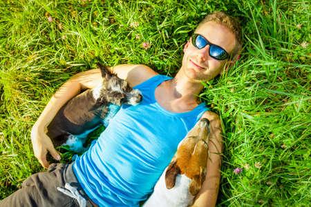 Jack-Russell-Hunde mit Besitzer auf der Wiese Gras im Park entspannen, zusammen umarmen und umarmt Standard-Bild