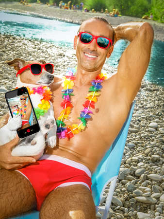 sunbath: jack russell dog with owner wearing funny fancy red sunglasses, lying on hammock or beach chair lounger together as lovers or friends, on summer vacation holidays taking a selfie together Stock Photo