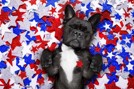 Französische Bulldogge, die eine Flagge von USA und Sieg oder Friedensfinger auf Unabhängigkeitstag 4. Juli weht